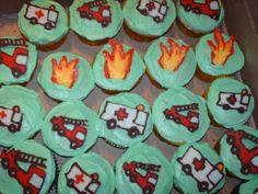emergency vehicles hand drawn with candy melts and used to top chocolate, banana, and peanut butter cupcakes covered in buttercream frosting.
