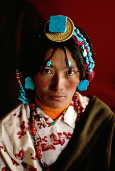 Asia | Portrait of a Tibetan woman wearing a traditional headdress with many strands of turqoise, Tagong, Tibet | © Steve McCurry