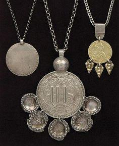 """Traditional silver pendants from Skåne. """"TRILLEKORS, PENNINGKORS och ELLAKORS, i silver Trillekorset med dekor av IHS och fyra skålformade hängen (delvis med skador och förstärkningar). Stämplar IA(?) (troligen Jonas Aspelin dy, verksam i Ystad 1796-1827). Penningkors i form av danskt mynt 24 sk """""""