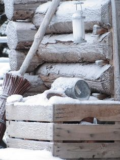 Primitive snowscape with log cabin, zinc flowerpot, wooden crate, broom, and lantern snow winter