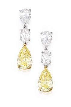 PAIR OF PLATINUM, 18 KARAT GOLD, FANCY INTENSE YELLOW DIAMOND AND DIAMOND EARRINGS Suspending two pear-shaped Fancy Intense Yellow diamonds weighing 3.05 and 2.40 carats, suspended by two pear-shaped diamonds weighing 1.02 and 1.01 carats, topped by two oval-shaped diamonds weighing .93 and .80 carat.