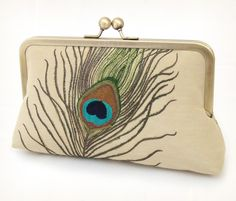 This stunning clutch features a beautiful embroidered peacock feather in teal, taupe and green on a pale gold linen, with delicate peacock feather det