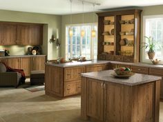 Rustic wood species and clean door styles give this kitchen an inviting,  comfortable look. Lyndale Rustic Cherry in Husk.