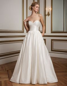 Justin Alexander wedding dresses style 8825 An elegant Silk Dupion ball gown with piped neckline and waistline, full gathered skirt and pockets create simplicity at its best.