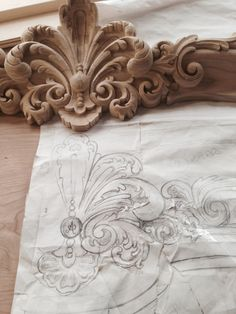 Detail of Hand carved fleur for curved bonnet on built in china cabinets for a Boiserie dining room. Drawing & hand carving shown here in raw domestic hard wood.  Manufactured & designed by Auffrance.