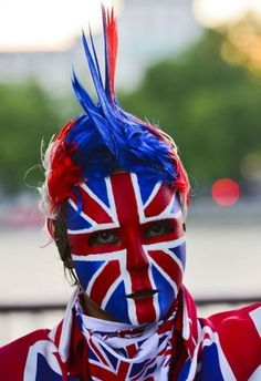 A women wears a British flag painted mask prior to the opening ceremony of the London 2012 Olympic Games.