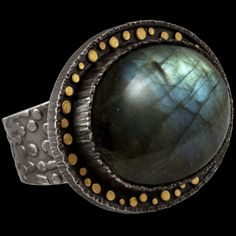 An oxidized sterling silver ring, with a broad textured band, a wide textured bezel with gold circles, and an oval labradorite cabochon