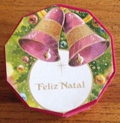 "A beautiful Brazilian ""Feliz Natal"" (Merry Christmas) 10-sided (decagon) red velvet box with a Christmas motif of red and gold bells, a cross, evergreens, multicolored Christmas ornaments and ribbons, and snow flakes embossed on the lid."