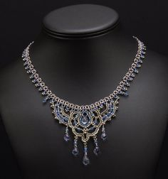 This beautiful and flowing bead woven necklace in shades of slate blue and matte silver features Tanzanite Quartz briolettes, icy Swarovski crystals and delicate details. Draping elegantly from your neck, this lovely necklace is reminiscent of medieval times and is made with the highest quality gemstone, crystal and seed beads available, and is hand sewn one tiny bead at a time. The focal element is suspended from a chain of right angle weave embellished with tiny steel beads. Slaying…
