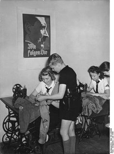 Members of the League of German Girls sewing in Berlin, Germany, Jul 1942; note boy with dagger and poster of Hitler 'We Follow You' on wall