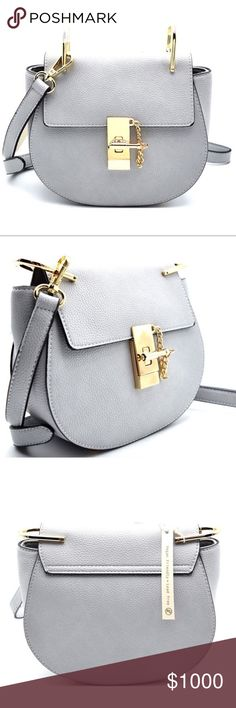 """Light Grey Saddle Bag with Goldtone Hardware Light Grey Pebble Vegan Leather Saddle Bag with Goldtone Hardware. Interior has 1 zipper slot and 1 pocket slot. Closure has a full zipper and flap with goldtone hardware toggle. Dimensions 8""""L x 3""""W x 7""""H. Price is FIRM Unless Bundled. Price will be $48 GlamVault Bags Crossbody Bags"""