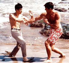 """Bruce Lee and Van Williams practicing some Kung-Fu on the Beach. Star together in """"The Green Hornet."""""""