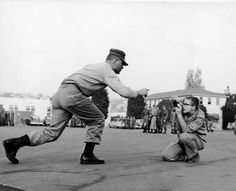 1955: Dickey Chapelle crouches on the ground as she takes a photograph of a Marine at the San Diego Recruit Depot.   Wisconsin Historical Society