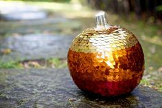 Sequin & Glitz Pumpkin  Materials: Sequins, glue gun, and a stapler  Method: I glued each sequin on the pumpkin individually and reinforced with a stapler once each row was done.