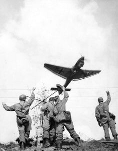 """German Luftwaffe Fallschirmjäger(paratroopers) waive to a passing Junkers Ju 87 dive bomber,also known as a Stuka, during the Battleof the Netherlands (codename: Fall Gelb, or """"Case Yellow"""").Near Venlo, Limburg, Netherlands. May 1940."""