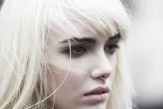 Ultra blonde hair with dark bold brows & nude lips