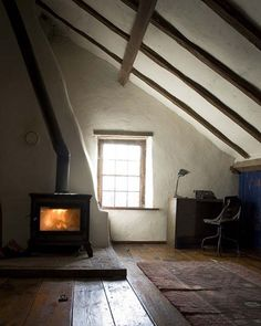 Attic apartment room with wood stove and exposed wood ceiling beams - Wide plank wood floors - Rustic interior