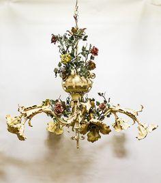 Hele grote oude hanglamp, te dateren rond de jaren 30 ongeveer. Een zogenaamde bloemen-kroonluchter. De lamp heeft 6 armen, die bloemkelken symboliseren. Verder is de lamp op diverse plaatsen versierd met metalen bloemen in roze en gele kleuren. Al met al een hele sierlijke en vrolijke lamp. Deze lamp is niet voor iedereen, je vindt hem vermoedelijk of helemaal te gek of juist niet. Let op; het is wel een hele grote lamp.