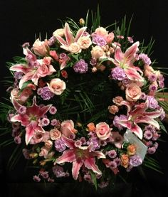 Sympathy wreath of stargazer lilies, pink roses, lavender poms and mini carnations by Alice Woodside Lynch for Bennett's Flowers, Jonesboro, AR.