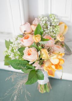 Spring wedding bouquet including garden roses, lilacs, ranunculas, sweet peas, parrot tulips and hypericum berries | 100 Layer Cake