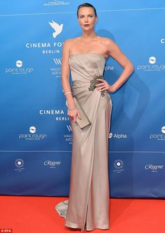 Elegantly hairless: Charlize Theron shines despite her buzz cut on the red carpet for the charity event Cinema For Peace in Berlin, Germany.