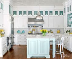 Storage is no struggle for this clean kitchen that features crisp white cabinets across three walls. Display cabinets with quintessential beach cottage blue interiors and frosted glass doors contribute the perfect pop of color. They take advantage of the kitchen's lofty ceilings, but plenty of upper cabinets ensure everyday essentials are close at hand.Layers of trim crown the soffit above the top cabinets, completing the built-in look.