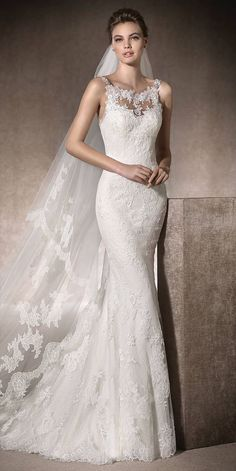 Romantic mermaid wedding dress with round neckline in tulle and embroidered tulle, with lace, Chantilly and guipure appliqués. Elegant gemstone embroidery on the sides of the back.