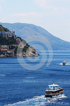 Photo about Some passenger boats are passing on the sea near an old town on the cliff. Image of small, blue, town - 92517525 Cliff, Old Town, Boats, Sea, Stock Photos, Blue, Image, Old City, Ships