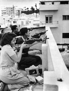 Irgun Zvai Leumi (National Military Organization in the Land of Israel) are armed with rifles, revolvers and automatic weapons as they take position on the rooftop of a Jewish house in case of Arab attack on the Jaffa – Tel Aviv border in the Manshiah Jewish quarter in Tel Aviv, Israel, on December 27, 1947.