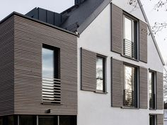 This house has modern window shutters that match the wooden siding used on the house.