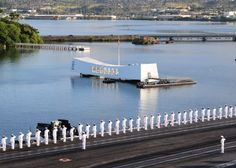 August 31, 2011: Sailors and Marines render honors as the aircraft carrier USS Ronald Reagan passes the USS Arizona Memorial while entering Pearl Harbor for a port visit. Ronald Reagan is in the U.S. 3rd Fleet area of responsibility. Photo: Seaman Apprentice Charles D. Gaddis IV. Caption: DVIDSHUB.