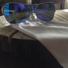 Mens Oakley sunglasses Mens Oakley sunglasses. With white soft protective case. Blue/purple lens. White frame. Few scratches on right lens. Oakley Accessories Sunglasses