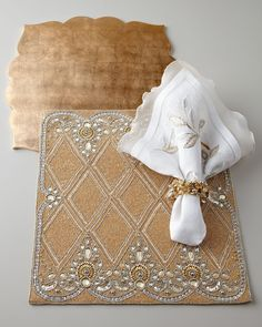 Kim Seybert Golden Placemats & White Napkins  An elegant combination of gold, silver, and white hues,