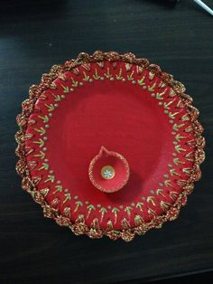 Pooja Thaali - 2 thermacol plates glued together....then coloured it using red fabric paint .....inserted holes at equal distance at the edge.....crocheted a border lace with gold & red yarn & then used gold glitter to design it....
