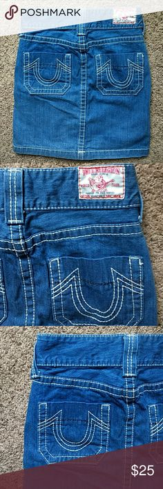 "True Religion Denim Skirt Lighter wash cotton denim skirt with white stitching around it has front and back pockets embroidery design on back pockets has never been worn is approx 18"" long from top to bottom hemline has a pleated design in front at the bottom True Religion Jeans"