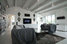 Solaio in legno e acciaio laccato, pavimento in rovere sbiancato, muro con mattoni a vista dipinti di bianco