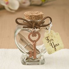 Charm your guests with a secret message written on a parchment scroll and placed inside a beautiful heart shaped clear glass jar. This is a sophisticated must-have favour for your next romantic celebration!