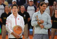 Rafael Nadal of Spain and  Kei Nishikori of Japan hold their trophies after Nishikori retired injured in the third set in their final match during day nine of the Mutua Madrid Open tennis tournament at the Caja Magica on May 11, 2014 in Madrid, Spain.