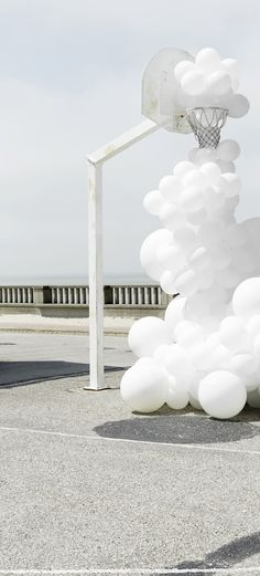 Invasions - Charles Pétillon, 2015. An art installation with white balloons invading public space. A weird balloon cloud passes through a white painted basketball hoop.
