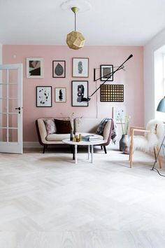 With a pink this subtle, there's no need to restrain yourself. Have the colour on your wall, in the prints on that wall and the fabrics of the couch and throw pillow. Brass touches and different picture frames add a certain richness to the look.