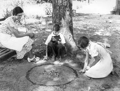 Playing marbles in the dirt...kids don't play much in the dirt anymore...gotta keep the hands clean to play video games...sad!