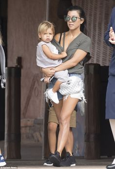 Casually cool: Kourtney looked casually cool as she carried her youngest child, Reign