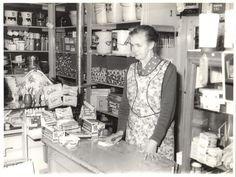 """In 1958 is deze foto gemaakt in winkel""""de Goede huishoudelijke artikelen""""aan de Middelweg 31 te Uitgeest.Mevr. de Goede-Velzeboer staat hier achter de toonbank."""