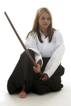 A girl holds a Bokken (Wooden Sword). Martial arts uses a man's hakama, even for women. One notable exception to this practice is archery.