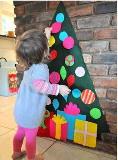 This felt Christmas tree and ornaments looks awesome in your home and will keep the kids busy as they decorate it ... and re-decorate it.  They can learn a lot about colours and shapes while decorating! #ChristmasCraftsForKids #ChristmasDecorIdeas #TickledMummyClub