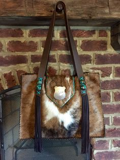The Buckaroo Tote, with turquoise stones and strap end fringe, and a vintage  badge on the flap. gowestdesigns.us