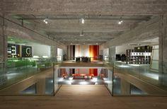 Bovenaan de trap: het hout, het glas en het ruwe beton in combinatie met het strakke kleurrijke meubilair.
