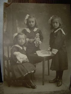 3 sisters with book and dolls