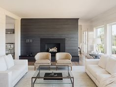 Living room with shiplap wall painted in a charcoal gray color. Sophie Metz Design.