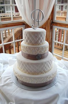 Fondant and  buttercream wedding cake, round, with pewter accents and ribbon, quilted texture